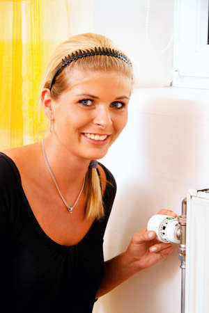 Woman with radiator. Save energy. Thermostat of the heater. Save on heating costs. Stock Photo - 9550531