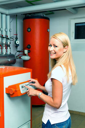 energy consumption: A young woman in the boiler room for heating. Save energy