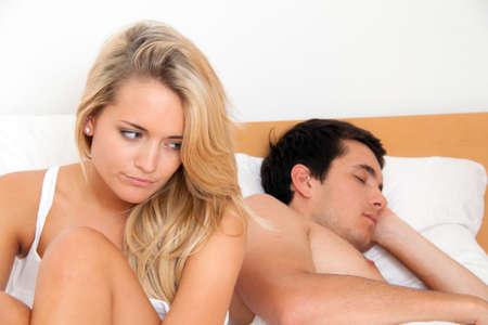 strife: Una giovane coppia a letto problemi e crisi. Divorzio e separazione.