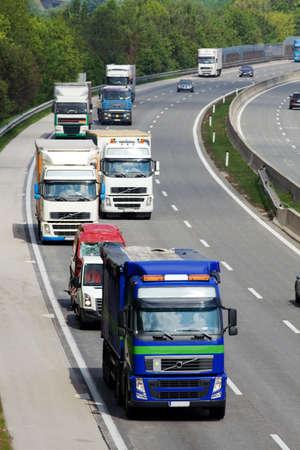 ciężarówka: Na drodze ciężarówek i samochodów jazdy obok siebie. Zdjęcie Seryjne