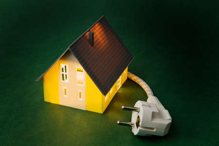 curren: An illuminated house with power plug. Energy in the household