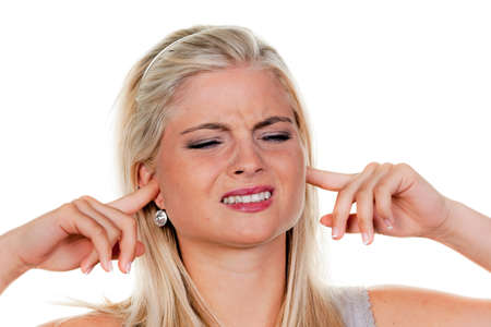 noise pollution: Young woman suffering from noise pollution, and holding her ears. Stock Photo