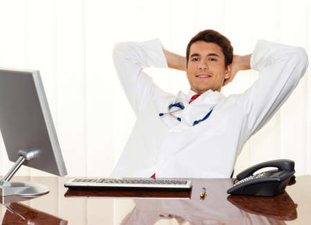 A successful young doctor sitting at desk and smiling. Stock Photo - 9637690