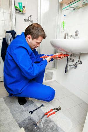 reparaturen: Ein Sanit�r-Reparatur defekte Waschbecken im Badezimmer