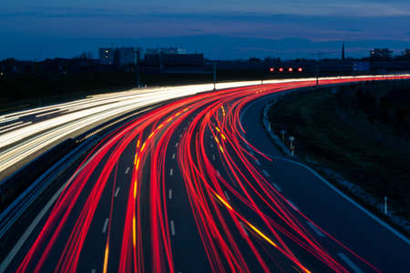 Many cars are driving at night on a highway and create light trails. photo