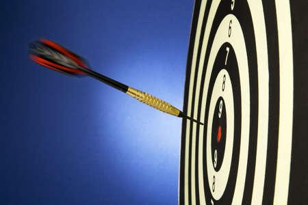 Portrait shot of a dart on bullseye of a dart board photo