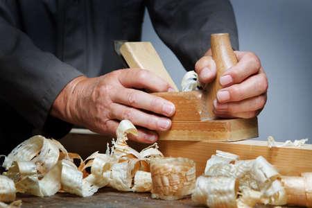 carpintero: Un carpintero con un virutas planer y madera en el taller.