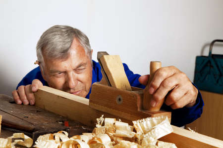 planer: A carpenter with a planer and wood shavings in the workshop.