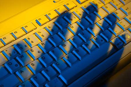 개인 정보 보호: Computer keyboard and the shadow of a hand. Theft of data.