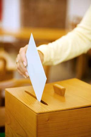 Une jeune femme dans une élection doit offrir leur vote. Bulletin de vote au scrutin. Banque d'images