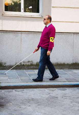 blind people: A blind man walks with a cane on a street