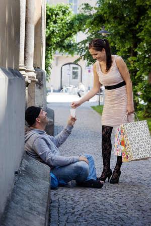 Eine junge, wohlhabende Frau verleiht Geld ein Bettler