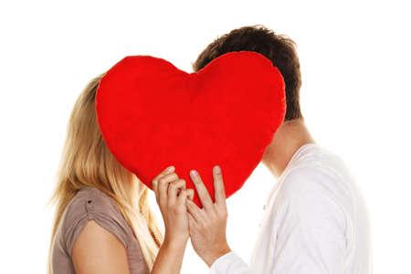 secret love: Loving couple kissing behind a heart. Love is beautiful. Secret love