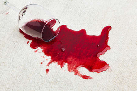 spills: Red wine is spilled on a carpet. Emptied the other glass