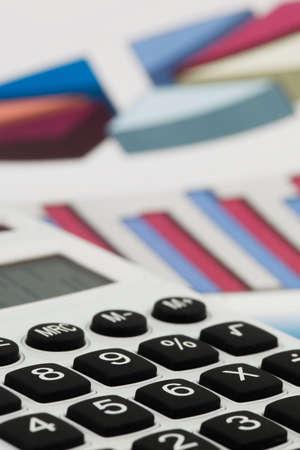 obligaciones: Una calculadora con gr�ficos de un balance. Ventas, ganancias y costos operacionales. Foto de archivo