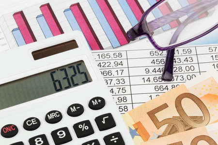 auditors: A calculator with graphics of a balance sheet. Sales, profit and operational costs.