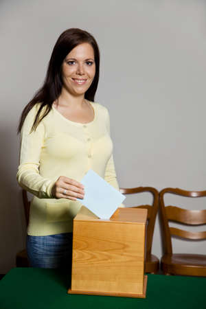 ballot papers: A young woman in an election shall deliver their vote. Ballot at the polling station.