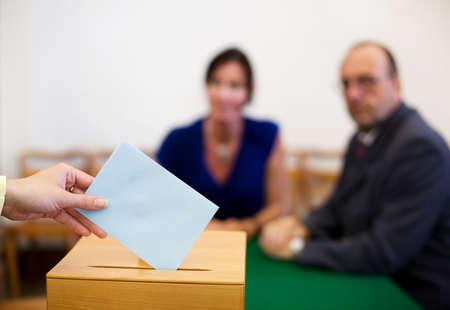 encuestando: Una mujer joven con un votante en la cabina de votaci�n. Votar en una democracia