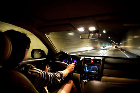 vrouw rijdt een auto in een snelwegtunnel