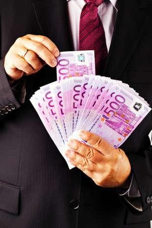 rendite: Un manager con un sacco di banconote da 500 euro in mano.