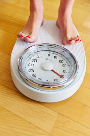 jung: Turn the feet of a woman standing on bathroom scales to Stock Photo