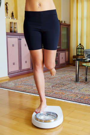 thinness: Turn the feet of a woman standing on bathroom scales to Stock Photo