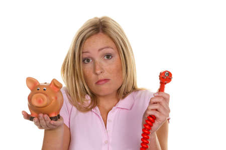A young woman holding a piggy bank and a power plug. Symbolic photo for energy cost Stock Photo
