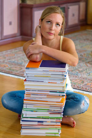 unsuspecting: A student sits in front of a stack of books to learn the