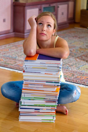 insipid: A student sits in front of a stack of books to learn the