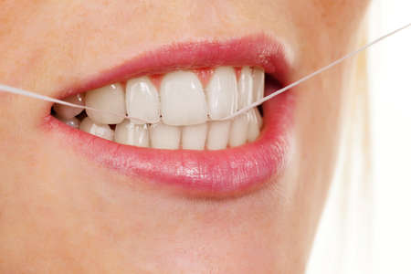A young woman uses dental floss to clean your teeth photo