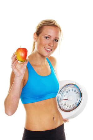thinness: Young woman with scales and apple. Successful Diet