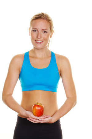 thinness: A young woman in sports clothing holding an apple in his hand Stock Photo