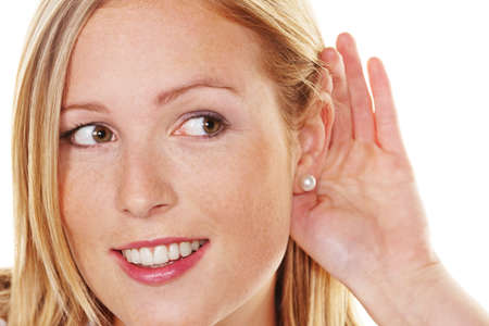 A young woman holds the hand behind the ear to listen. Stock Photo - 10486769