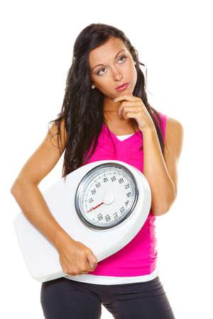 Een jonge vrouw is ontevreden met uw lichaamsgewicht. Proberen om lichter op de weegschaal.