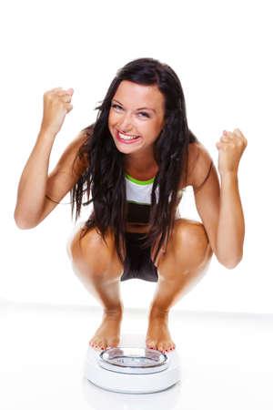 Una mujer joven con un equilibrio en la mano, sonriendo después de una dieta exitosa
