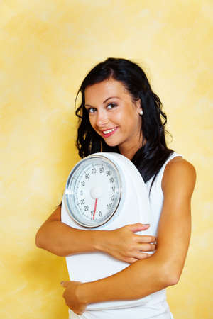 thinness: A young woman with a balance in his hand smiling after a successful diet