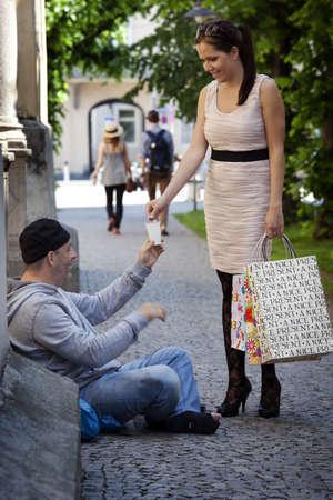 obligaciones: Una mujer joven rico le da algo de dinero mendigo