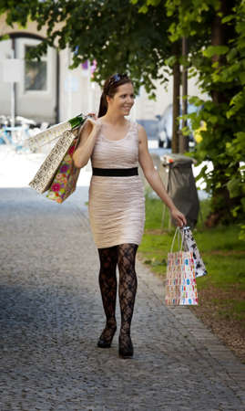 A young woman carrying shopping bags while shopping. Stock Photo - 10514224