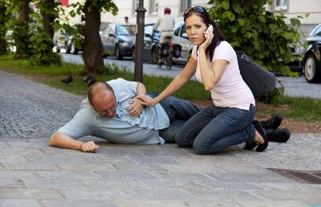 hartaanval: Een man heeft een hartaanval of een beroerte op de weg Stockfoto