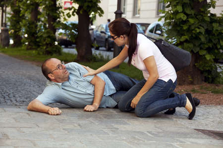 ataque al corazón: Un hombre tiene un ataque al corazón o un derrame cerebral en el camino Foto de archivo