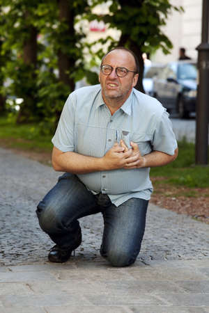 cardiac arrest: A man has a heart attack or stroke on the road Stock Photo