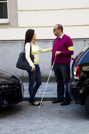 A young woman helps a blind man across the street.