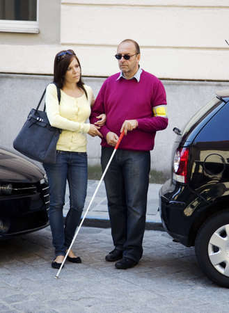 myopic: A young woman helps a blind man across the street.