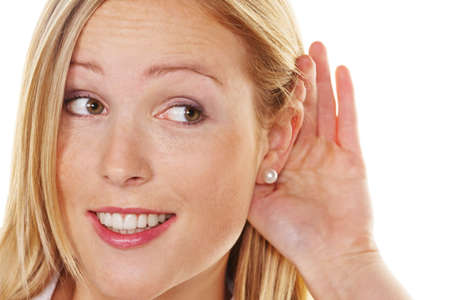 premiums: A young woman holds the hand behind the ear to listen.