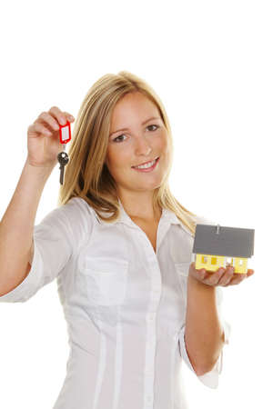 A young woman with a model house and apartment keys. photo