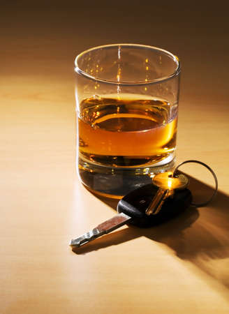 Car keys and a glass of alcohol on a table photo