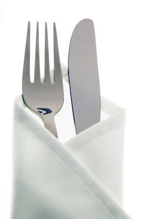 covered: A knife with a fork and plate. Place setting for a dinner at the restaurant.