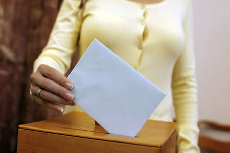 state election: A young woman with a voter in the voting booth. Voting in a democracy