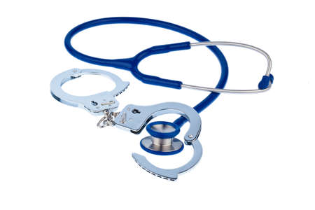 physicans: Handcuffs and a stethoscope lying on a white background. Stock Photo