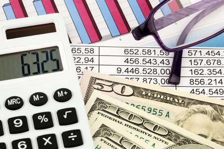 liquidity: A calculator and dollar bills lying on a Statistical Stock Photo
